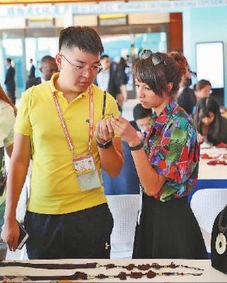 在2018年中非合作论坛北京峰会新闻中心,外媒记者向中国传统文化传承人了解团扇制作技艺