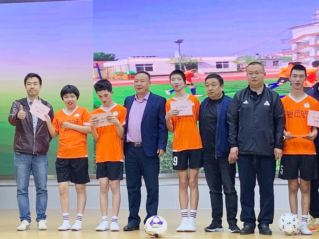 天津美信集团副总裁程建奇校友(左四)等为残疾孩子们颁发公益金